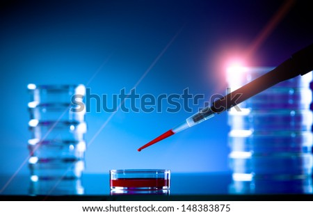 pipette and petri dish on a glass table in the lab - stock photo