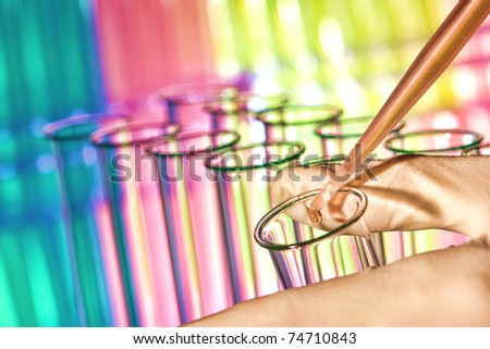 Pipette filled with red chemical and drop of liquid over laboratory glass test tubes in scientist hand for a chemistry experiment in a science research lab - stock photo