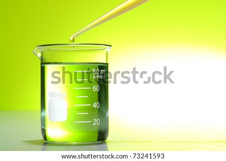 Pipette with drop of chemical above a glass scientific beaker with green liquid over bright yellow background for a laboratory chemistry experiment in a science research lab - stock photo