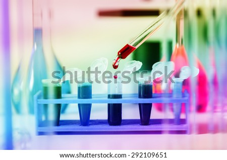 Pipette with drop of color liquid and microtubes.Blood samples for research in microtubes. - stock photo