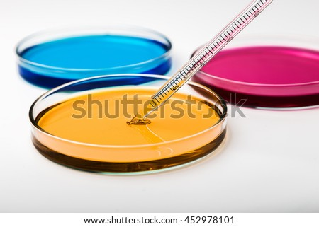 Pipette with drop of color liquid and petri dishes. - stock photo
