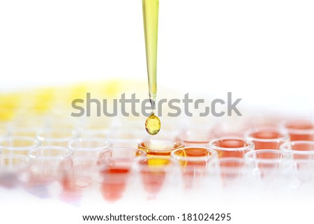 Pipette with drop of liquid over test tubes - stock photo