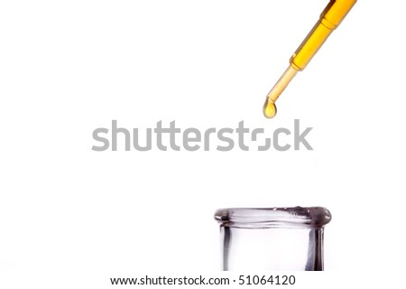 Pipette with droplet of liquid above glass flask - stock photo