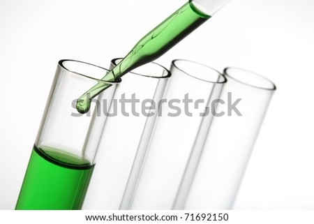 Pipette with emerging drop of liquid over test tubes - stock photo