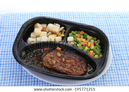 Piping hot Chopped steak microwave dinner in black plastic tray on white plate against blue gingham place mat.  New potatoes and vegetable medley side dishes. - stock photo