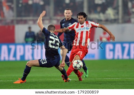 PIRAEUS, GREECE -FEB. 25. Olympiakos' Alejandro Dominguez, fights for the ball with Manchester United's Antonio Valencia during their Champions League soccer match, in Piraeus Feb. 25, 2014 - stock photo