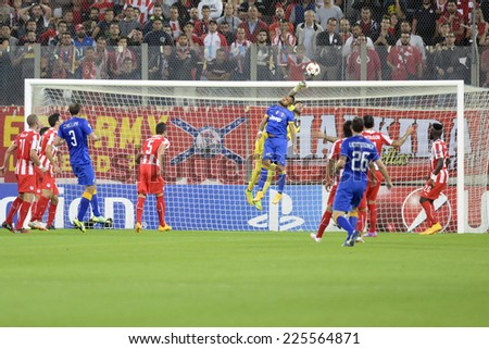 Piraeus, Greece Oct. 22, 2014. Olympiacos' goalkeeper Roberto saves on a attempt to score by Juventus' Carlos Tevez, during a Champions League soccer match between Olympiakos and Juventus. - stock photo
