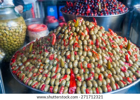 Piramidal heap of green olives and red pepper in a Sicilian public market - stock photo