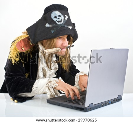 pirate attacking with a knife a laptop computer - stock photo