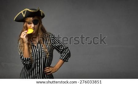 pirate biting chocolate gold doubloon, dark background - stock photo