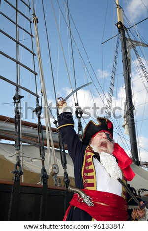 Pirate captain in colorful traditional costume stands on board ship, shouts, and waves his sword. Sailing ship rigging and blue sky in background, vertical layout. - stock photo