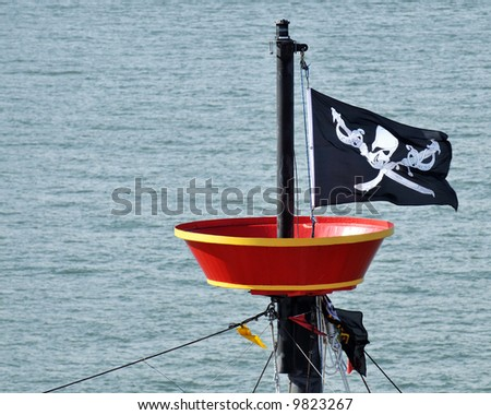 Pirate flag flying from a ship's mast. - stock photo