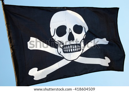 Pirate flag of skull and crossbones, flying on a clear blue sky - stock photo