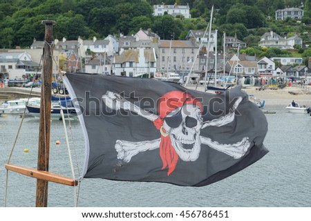 Pirate flag on a boat in Lyme Regis - stock photo