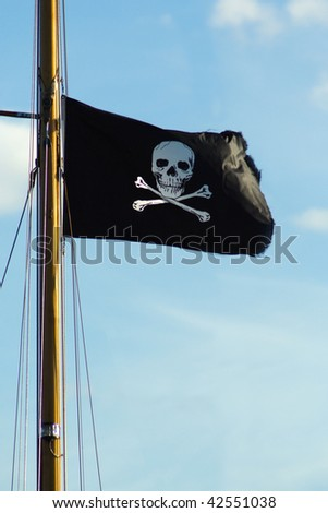 Pirate ship flag of the Skull and Crossbones. - stock photo