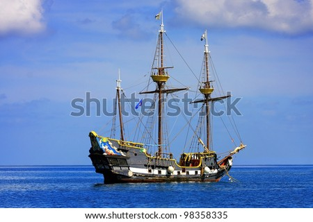 Pirate ship in a blue water - stock photo
