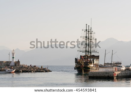 Pirate ship in the port with a lighthouse - stock photo
