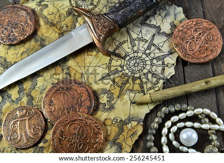 Pirate still life with decorated dagger, map, ancient coins and pearl necklace on wooden background - stock photo