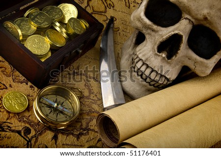 Pirate treasure. Old brass compass lying on a very old map with treasure chest full of golden coins, skull and knife - stock photo