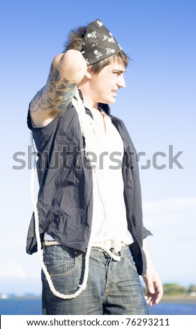 Pirate With Tattoos Holds A Rope When Docking His Ship In A Seaside Portrait - stock photo