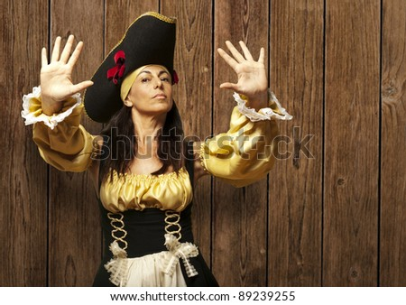 pirate woman gesturing stop against a wooden wall - stock photo
