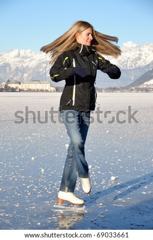Pirouette of young woman figure skating at frozen lake of zell am see in austria