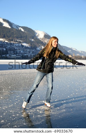 Pirouette of young woman figure skating at frozen lake of zell am see in austria - stock photo