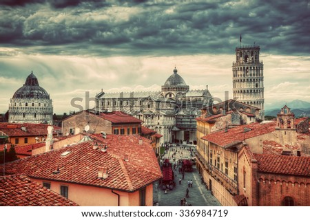 Pisa Cathedral with the Leaning Tower panorama. Unique vintage perspestive from rooftop, dark clouds. Tuscany, Italy - stock photo