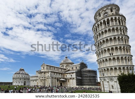 PISA, ITALY SEPTEMBER 3, 2014: Tourists in the Piazza dei Miracoli, having from left to right the Baptistry, the Cathedral and the Bell Tower. - stock photo