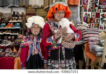 PISAC, PERU - SEPTEMBER 25,2015: Unidentified children with a lamb at Pisac market in Peru. Pisac is a village well known for its market every Sunday, Tuesday and Thursday.