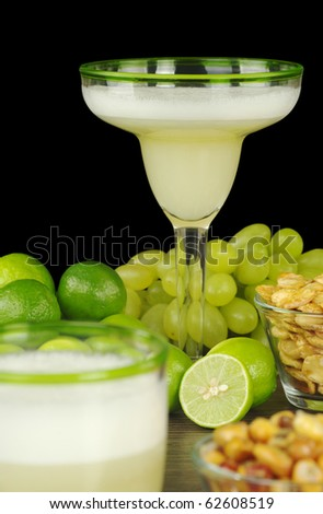 Pisco Sour, a Peruvian cocktail made of pisco, lime juice, sugar syrup and egg white. The cocktail is surrounded by grapes, limes, and Peruvian snacks (Selective Focus, Focus on the glass in the back)