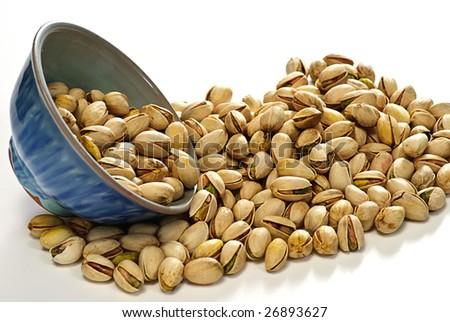 pistachio and pot on white - stock photo
