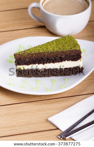 Pistachio cheesecake, mousse cake with nuts and hot drink decoration on a wooden table - stock photo