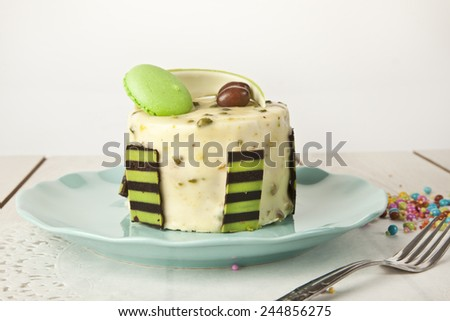 Pistachio cheesecake, mousse cake with nuts decoration on a white plate - stock photo