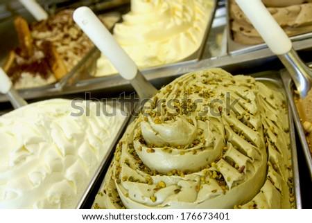 Pistachio ice cream and cream flavors are shown inside an italian ice cream parlor. - stock photo