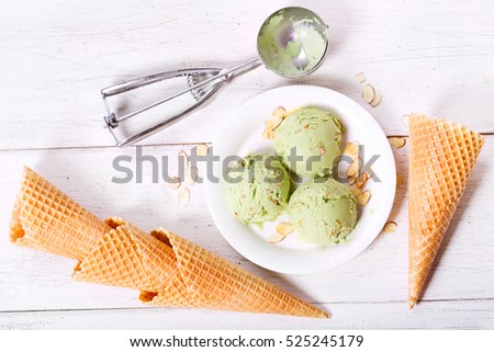 pistachio ice cream scoops on wooden background, top view