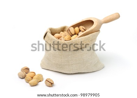 Pistachio in textile sack with scoop on white background - stock photo
