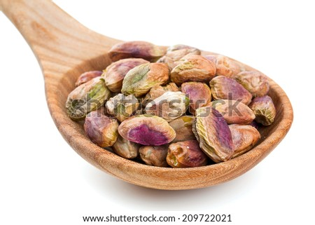 pistachio in wooden spoon, isolated on white - stock photo