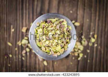 Pistachio Kernels (minced; close-up shot; selective focus) on vintage background