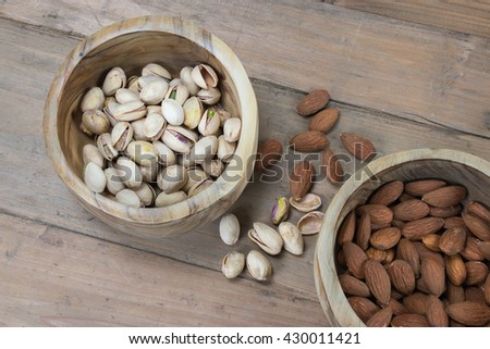 Pistachio nuts and Almonds in wooden bowl on rustic background. - stock photo