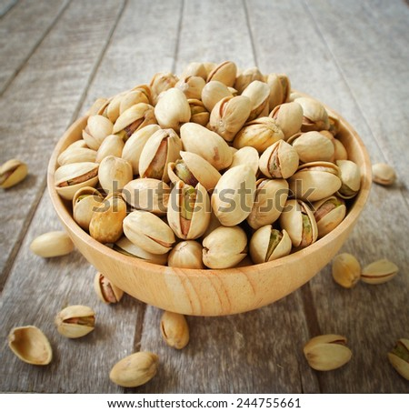 Pistachio nuts in wood cup ,closeup - stock photo