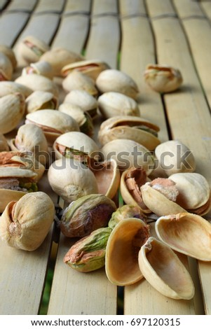 Pistachio nuts on bamboo table. Vertical image.