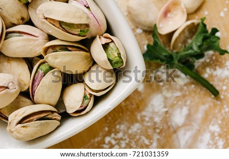 pistachio nuts on the white bowl