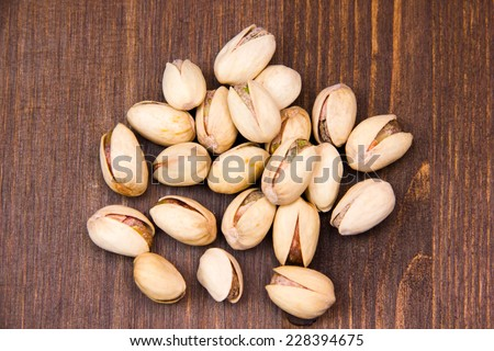 Pistachio nuts on wooden table seen from above - stock photo