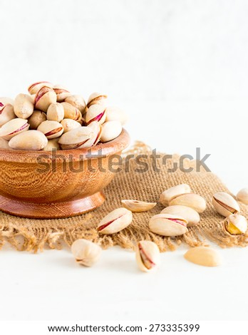 Pistachio  Pistachio Nuts filled in a wooden bowl , isolated on a white background - stock photo