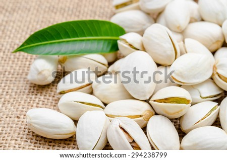 Pistachios and green leaf on sack background. - stock photo