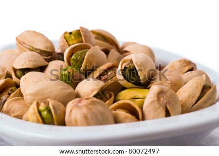 pistachios in a bowl on the table isolated on white background - stock photo