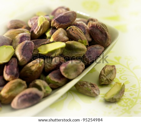 pistachios in a white bowl on a green floral table cloth - stock photo