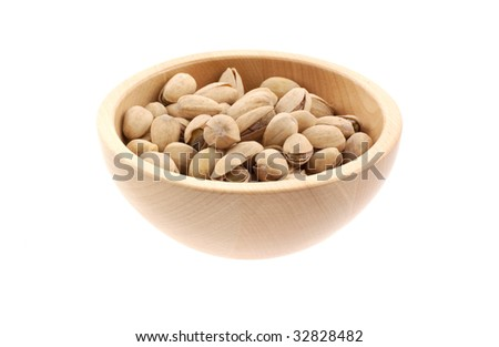 pistachios in a wood bowl. white background - stock photo
