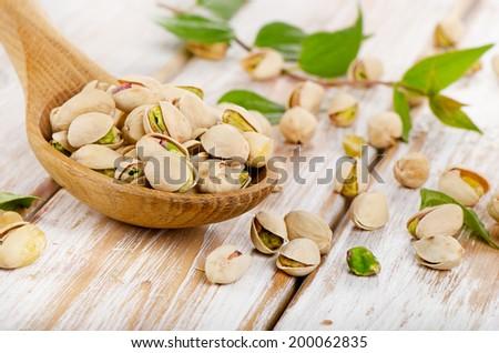 Pistachios in a wooden spoon. Selective focus - stock photo